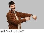 Купить «smiling young man with smart watch», фото № 33444629, снято 22 февраля 2020 г. (c) Syda Productions / Фотобанк Лори