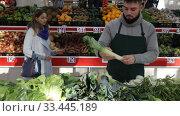 Shopping assistant puts leek on supermarket counter. Стоковое видео, видеограф Яков Филимонов / Фотобанк Лори