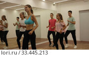 Купить «Group of teenagers participating in dance class, following their young female teacher in dance school», видеоролик № 33445213, снято 21 сентября 2019 г. (c) Яков Филимонов / Фотобанк Лори