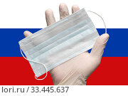 Купить «Doctor holds face mask in hand in white medical gloves on background colors flag of Russia. Concept pandemic insurance coronavirus», фото № 33445637, снято 25 марта 2020 г. (c) А. А. Пирагис / Фотобанк Лори