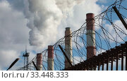 Factory chimneys smoke thick smoke and steam behind a fence with barbed wire, industry and pollution concept. Стоковое видео, видеограф Алексей Кузнецов / Фотобанк Лори