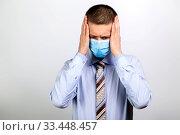 Купить «A business man in a mask grabbed his head with his hands», фото № 33448457, снято 26 марта 2020 г. (c) Владимир Арсентьев / Фотобанк Лори
