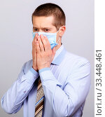Купить «A business man in a mask grabbed his face with his hands», фото № 33448461, снято 26 марта 2020 г. (c) Владимир Арсентьев / Фотобанк Лори