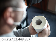A masked man is holding a roll of toilet paper in his hands. Selective focus. Panic and shortage in stores in the World Pandemic Coronavirus. Стоковое фото, фотограф Tetiana Chugunova / Фотобанк Лори