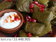 Купить «Dolma in a clay plate with pomegranate, sour cream and chacha on a wooden background», фото № 33448905, снято 23 марта 2020 г. (c) Марина Володько / Фотобанк Лори