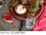 Купить «Dolma in a clay plate with pomegranate, sour cream and chacha on a wooden background», фото № 33448909, снято 23 марта 2020 г. (c) Марина Володько / Фотобанк Лори