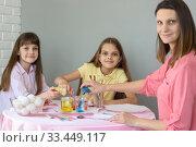 Купить «Мама и две дочки засыпают краситель в стаканы с водой», фото № 33449117, снято 28 марта 2020 г. (c) Иванов Алексей / Фотобанк Лори