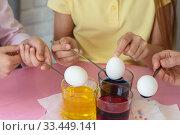 Купить «Руки опускают куриные яйца в раствор с красителем», фото № 33449141, снято 28 марта 2020 г. (c) Иванов Алексей / Фотобанк Лори