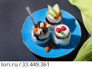 Купить «Sweet tasty milk curd creamy food in a glass jar of homemade breakfast. Cheesecake, English Trifle, Eton dessert, tiramisu, zuppa Inglese with nuts, almonds, cashews, hazelnuts, candied fruits and chocolate sauce», фото № 33449361, снято 14 декабря 2019 г. (c) Светлана Евграфова / Фотобанк Лори