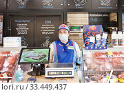 Продавец в магазине во время эпидемии с маской. Редакционное фото, фотограф Victoria Demidova / Фотобанк Лори