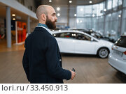 Купить «Smiling man poses in car dealership», фото № 33450913, снято 15 декабря 2019 г. (c) Tryapitsyn Sergiy / Фотобанк Лори