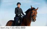 Купить «Horse riding - beautiful woman with a straight posture sits astride a horse», видеоролик № 33450989, снято 4 июня 2020 г. (c) Константин Шишкин / Фотобанк Лори