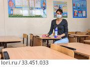Девушка моет чистящим средством парты в школе (2020 год). Редакционное фото, фотограф Иванов Алексей / Фотобанк Лори