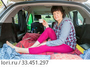 A beautiful mature woman peeks out the back door of a car, where she sits and drinks tea during a car trip on a sunny summer day. Стоковое фото, фотограф Акиньшин Владимир / Фотобанк Лори