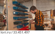 Купить «A man worker choosing screws from the stand in the carpentry workshop», видеоролик № 33451497, снято 27 мая 2020 г. (c) Константин Шишкин / Фотобанк Лори