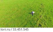 Купить «Low orbital flight around man on green grass with notebook pad at yellow rural field.», видеоролик № 33451545, снято 18 марта 2019 г. (c) Александр Маркин / Фотобанк Лори