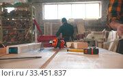 Купить «Men working in the carpentry workshop - different items on the table», видеоролик № 33451837, снято 2 июня 2020 г. (c) Константин Шишкин / Фотобанк Лори