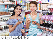 Купить «Girl with mother choosing lipstick in cosmetics shop», фото № 33451845, снято 21 июня 2018 г. (c) Яков Филимонов / Фотобанк Лори