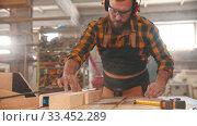 Купить «Man worker putting on headphones and starts cutting a piece of wood with a circular saw», видеоролик № 33452289, снято 2 июня 2020 г. (c) Константин Шишкин / Фотобанк Лори