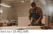 Купить «Carpentry industry - man worker sets up the grinding machine on the table», видеоролик № 33452645, снято 2 июня 2020 г. (c) Константин Шишкин / Фотобанк Лори