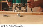 Купить «Carpentry industry - man worker in protective glasses and headphones cutting out the patterns out of the wooden plank», видеоролик № 33452729, снято 2 июня 2020 г. (c) Константин Шишкин / Фотобанк Лори