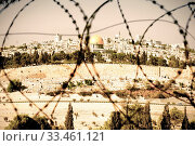 Купить «View from the Mount of Olives on the dome of the rock and ancient cemetery through the barbed wire, as a symbol of Palestine Israeli conflict. Retro style», фото № 33461121, снято 31 марта 2020 г. (c) easy Fotostock / Фотобанк Лори