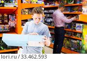 Купить «Teenager shopping in toy store», фото № 33462593, снято 27 мая 2020 г. (c) Яков Филимонов / Фотобанк Лори