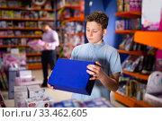 Купить «Teenager shopping in toy store», фото № 33462605, снято 27 мая 2020 г. (c) Яков Филимонов / Фотобанк Лори