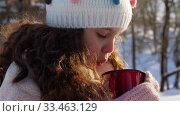 Купить «little girl with cup of hot tea in winter park», видеоролик № 33463129, снято 9 марта 2020 г. (c) Syda Productions / Фотобанк Лори