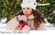 Купить «little girl drinking hot tea in winter park», видеоролик № 33463137, снято 9 марта 2020 г. (c) Syda Productions / Фотобанк Лори