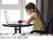 Купить «Девочка в медицинской маске смотрит онлайн урок в ноутбуке», фото № 33463581, снято 30 марта 2020 г. (c) Иванов Алексей / Фотобанк Лори
