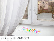 """A list of paper  with """"Stay Home"""" hashtag on white window sill. Стоковое фото, фотограф Юлия Кузнецова / Фотобанк Лори"""