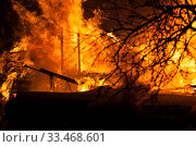 Купить «Burning fire flame on wooden house roof», фото № 33468601, снято 18 марта 2018 г. (c) Илья Андриянов / Фотобанк Лори