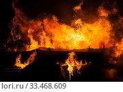 Купить «Burning fire flame on wooden house roof», фото № 33468609, снято 18 марта 2018 г. (c) Илья Андриянов / Фотобанк Лори