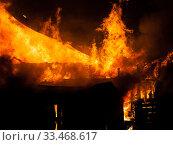 Купить «Burning fire flame on wooden house roof», фото № 33468617, снято 18 марта 2018 г. (c) Илья Андриянов / Фотобанк Лори