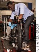 Afro american worker fixing failed motorcycle in workshop. Стоковое фото, фотограф Яков Филимонов / Фотобанк Лори