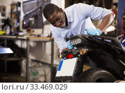 Afro american worker inspects the wheel of a motorcycle. Стоковое фото, фотограф Яков Филимонов / Фотобанк Лори