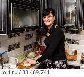 Купить «Красивая женщина готовит еду на кухне», эксклюзивное фото № 33469741, снято 9 марта 2020 г. (c) Игорь Низов / Фотобанк Лори