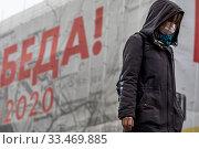 Женщина в медицинской маске идет по улице Новый Арбат в центре города Москвы во время распространения эпидемии коронавируса COVID-19 в России (2020 год). Редакционное фото, фотограф Николай Винокуров / Фотобанк Лори
