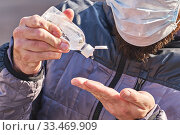 Man wearing mask uses antibacterial gel on hands, closeup. Стоковое фото, фотограф Kira_Yan / Фотобанк Лори