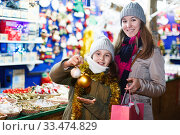 Smiling girl with woman are showing toys for X-mas tree. Стоковое фото, фотограф Яков Филимонов / Фотобанк Лори