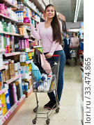 Купить «Cheerful woman standing with shopping cart», фото № 33474865, снято 5 апреля 2020 г. (c) Яков Филимонов / Фотобанк Лори
