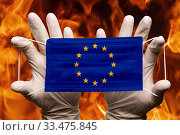 Купить «Doctor holding in white gloves protection medical face mask, respiratory bandage with European Union EU flag superimposed on mask. Concept», фото № 33475845, снято 25 марта 2020 г. (c) А. А. Пирагис / Фотобанк Лори