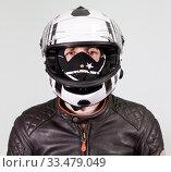Portrait of motorcyclist driver wearing crash helmet, dust facial mask, leather brown jacket, a grey background, looking at camera. Стоковое фото, фотограф Кекяляйнен Андрей / Фотобанк Лори