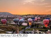 Купить «Preparing the balloons for flight at sunrise in Cappadocia, Turkey», фото № 33479353, снято 20 мая 2015 г. (c) Наталья Волкова / Фотобанк Лори