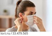 Купить «young woman wearing protective medical mask», фото № 33479565, снято 13 марта 2020 г. (c) Syda Productions / Фотобанк Лори
