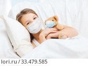 Купить «girl wearing medical mask with teddy bear in bed», фото № 33479585, снято 9 октября 2013 г. (c) Syda Productions / Фотобанк Лори
