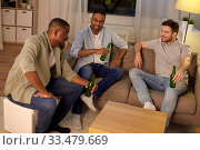 Купить «happy male friends drinking beer at home at night», фото № 33479669, снято 28 декабря 2019 г. (c) Syda Productions / Фотобанк Лори
