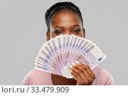 Купить «african american woman hiding behind euro money», фото № 33479909, снято 26 января 2020 г. (c) Syda Productions / Фотобанк Лори