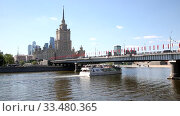Купить «View of the Radisson Royal hotel, Novoarbatsky bridge and floating on the Moscow river modern tourist boat. Moscow, Russia», видеоролик № 33480365, снято 3 апреля 2020 г. (c) Наталья Волкова / Фотобанк Лори